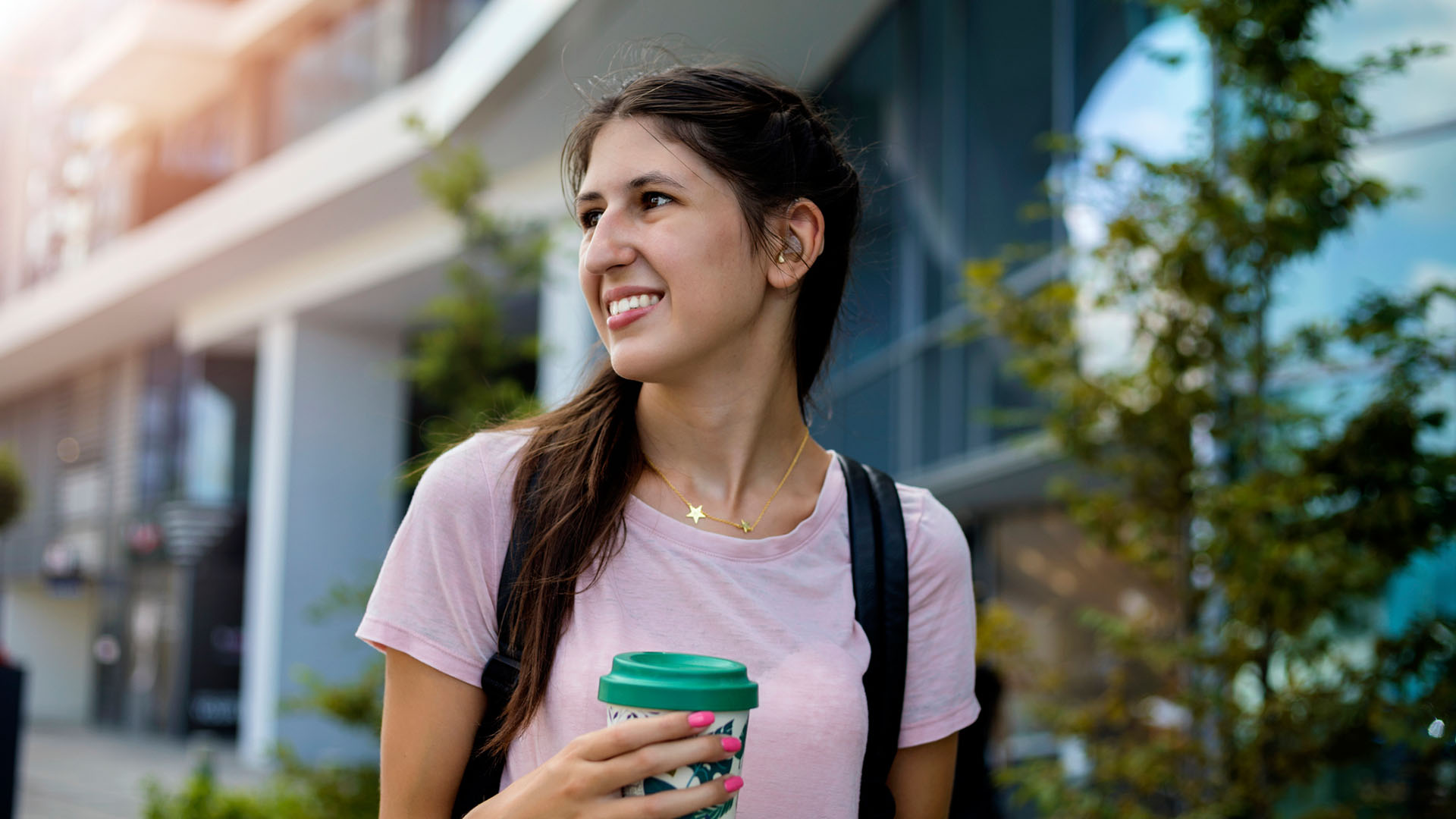 A smiling student walking through campus drinking coffee. She is equipped with a hearing aid.